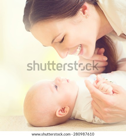 Mother and her Newborn Baby. Happy Mother and Baby kissing and hugging. Resting in bed together. High key soft image of Beautiful Family. Maternity concept. Parenthood. Motherhood  - stock photo