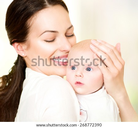 Mother and her Newborn Baby together. Happy Mother and Baby kissing and hugging. Beautiful Family. Maternity concept. Parenthood. Motherhood  - stock photo