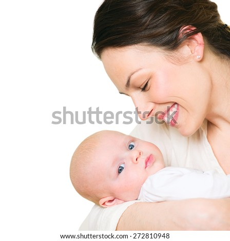 Mother and her Newborn Baby together. Love. Happy Mother and Baby kissing and hugging, isolated on white background. High key soft image of Beautiful Family. Maternity concept. Parenthood. Motherhood