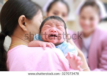 Mother and  her newborn baby with nurses,Happy cheerful moment. - stock photo