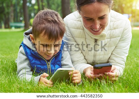 Mother and her small son are enjoying a nice day in park lying on green grass and playing on their smart devices - stock photo