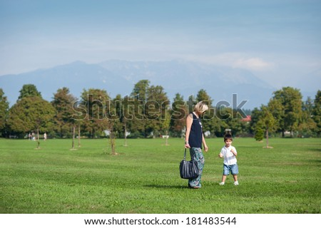 Mother and her son are having fun in park - stock photo