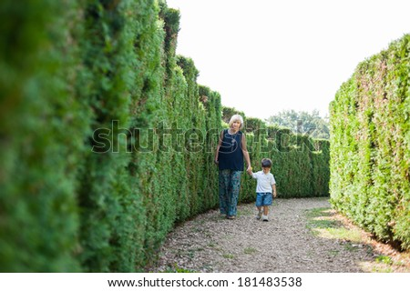 Mother and her son are walking in the beautiful park - stock photo