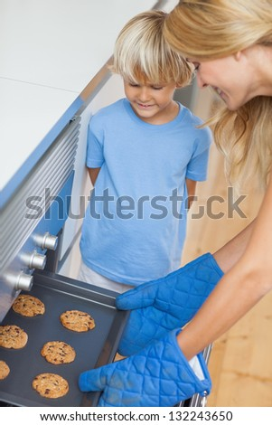Mother and her son baking cookies in the kitchen