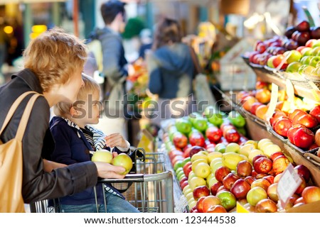 mother and her son buying fruits at a farmers market - stock photo