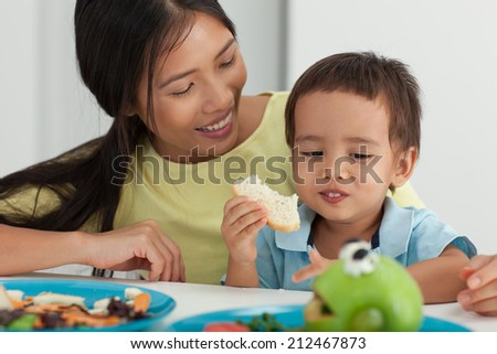 Mother and her son having breakfast together.