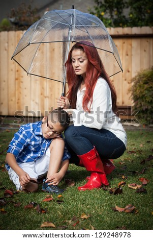 Mother and her son in the rain on a sunny day under an umbrella - stock photo
