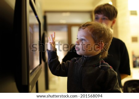 Mother and her son playing with touch screen in a museum - stock photo