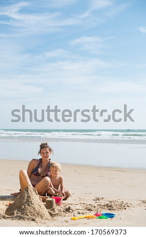 Mother and her son posing on the beach