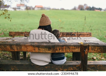 Mother and her son sitting on the wooden bench in countryside  - stock photo