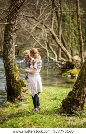 Mother and her son standing by the river - stock photo