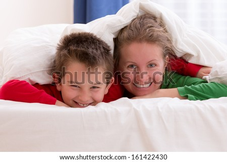 Mother and her son under the blanket with Christmas color pajamas, smiling to you while having great moments - stock photo