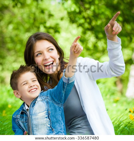 Mother and her son with book sitting on green grass pointing hand gesture in park. Concept of happy family relations and carefree leisure time - stock photo