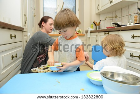 Mother and her sons making muffins together