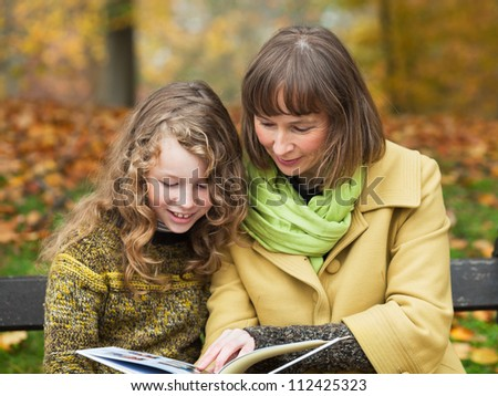 Mother and her teenager daughter sitting with a book on a bench in an autumn park