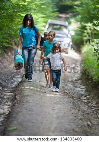 Mother and her three children hiking on road in woods. Car on background.