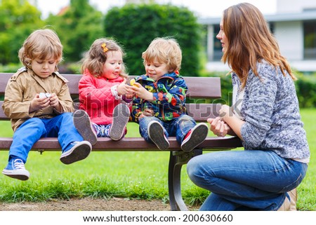 Mother and her three children in summer park, two little boys and adorable girl - stock photo