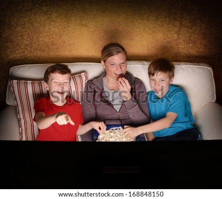 Mother and her two boys watching a comedy Movie at home - stock photo