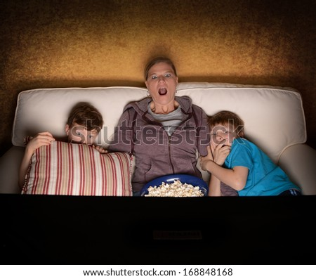 Mother and her two boys watching a Scary or Suspense Movie at home - stock photo