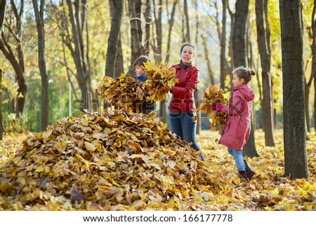 Mother and her two children gather fallen leaves in one big heap in autumn park - stock photo