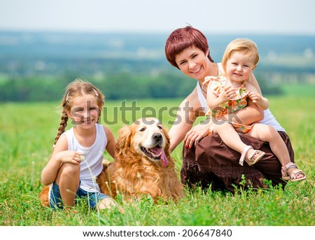 Mother and her two daughters in the park with a golden retriever dog - stock photo