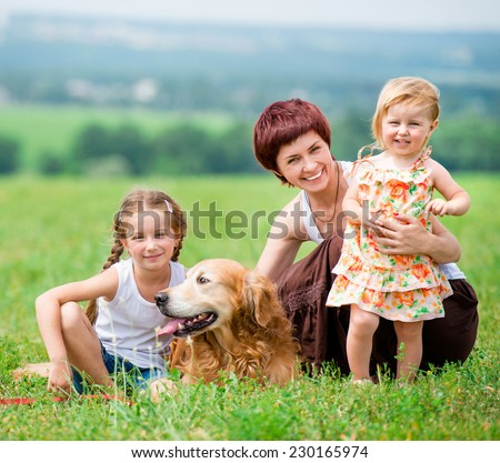 Mother and her two daughters in the park with a golden retriever dog. Beautiful family. looking at the camera. - stock photo