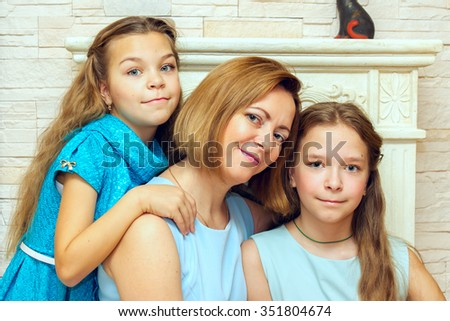 Mother and her two daughters sitting near the fireplace. Family portrait.