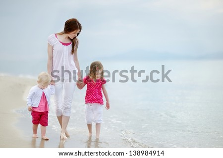 Mother and her two girls walking along a beach - stock photo