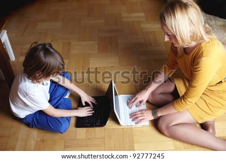 Mother and her 6 year old son working or playing on two small laptops