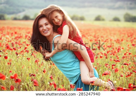 Mother and her 7 years old preteen child playing in spring poppy field in soft sunlight - stock photo