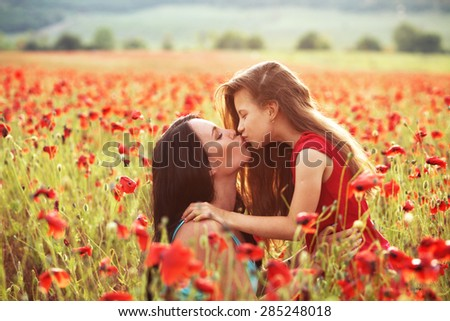 Mother and her 7 years old preteen child playing in spring poppy field in soft sunlight. Daughter kissing mom. - stock photo