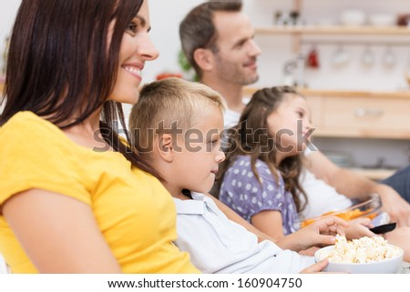 Mother and her young son watching television sitting close together on the sofa with the father and a young boy alongside them - stock photo