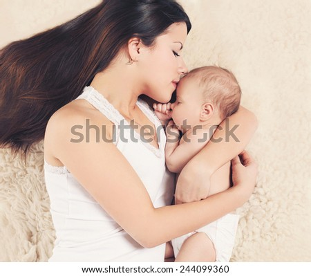 Mother and infant sleeping together on the bed at home, top view - stock photo