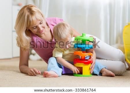 mother and kid child boy playing with colorful logical toy