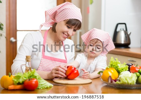 mother and kid daughter cooking in the kitchen - stock photo