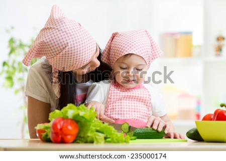 Mother and kid daughter knife cut cucumber