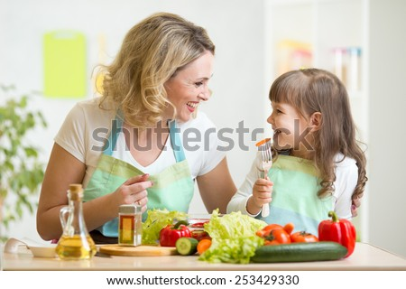 mother and kid daughter preparing healthy food and having fun - stock photo