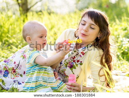 mother and kid girl having fun outdoors - stock photo