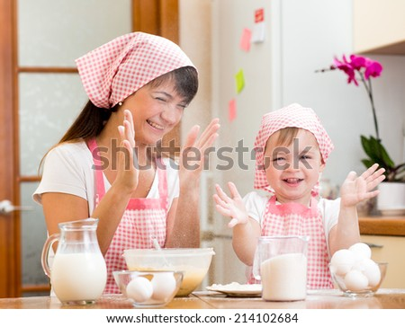 Mother and kid have fun preparing cookies at kitchen - stock photo