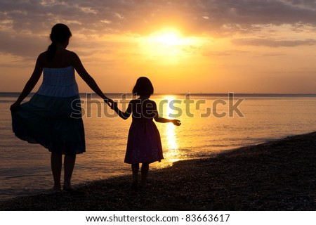 Mother and kid on sunset beach - stock photo