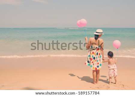 Mother and  kid on the beach with pink balloons vintage , happy mothers day vintage retro style  - stock photo