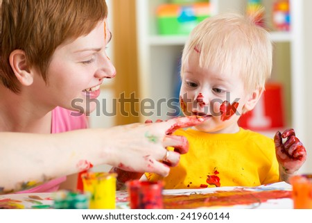 mother and kid son have fun with paints at home - stock photo