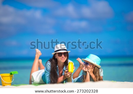 Mother and kid with suntan lotion on tropical beach - stock photo