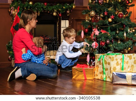 mother and kids decorating home at christmas, family christmas celebration - stock photo