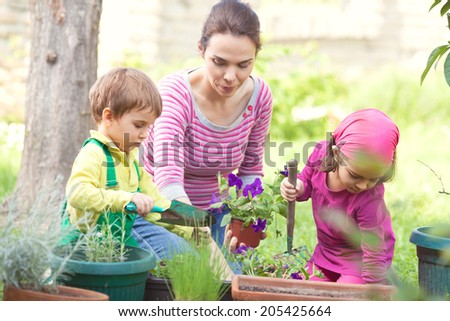 Mother and kids gardening - stock photo