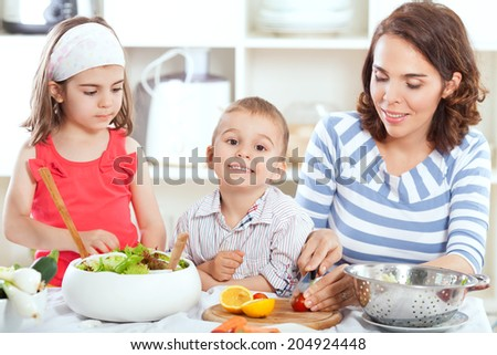 Mother and kids having fun in the kitchen making salad - stock photo