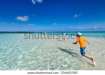 Mother and kids on a remote tropical beach enjoying tropical summer vacation - stock photo
