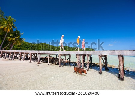 Mother and kids on a tropical beach enjoying summer vacation - stock photo