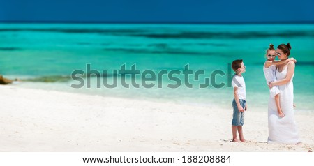 Mother and kids on a tropical beach vacation - stock photo