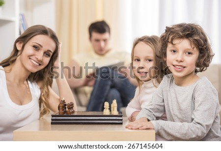 Mother and kids playing chess in living room. Father using a tablet on the couch. - stock photo